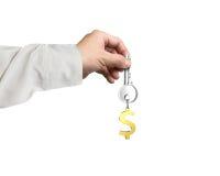 Hand die zilveren sleutel met gouden de vormsleutelring van het dollarteken houden Royalty-vrije Stock Foto