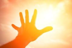 Hand, die zum Sonnenscheinhimmel erreicht. Stockfotografie