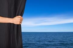 Hand die zwart gordijn met overzees en hemel openen achter het Stock Afbeelding
