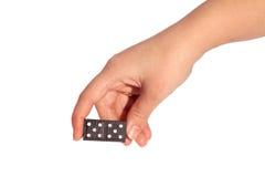 Hand die zwarte domino houden Stock Foto's