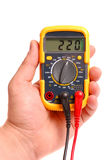 Hand with a digital multimeter on a white. Background royalty free stock images