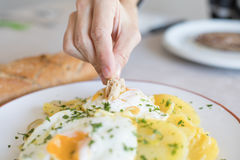 Hand diping bread in yolk of fried egg with potatoes Stock Images