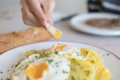 Hand diping bread into yolk of fried egg Royalty Free Stock Images