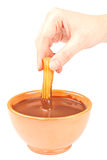 Hand Dipping a Churro in Chocolate. A hand dipping one Spanish churro in a cup of instant hot chocolate with milk. Typical food of Spain. On white Royalty Free Stock Photo