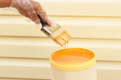 Hand dipping paint brush into a can Royalty Free Stock Photos