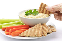 Hand dipping pita in hummus Royalty Free Stock Photos