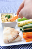 Hand dipping raw carrot stick into healthy dip Royalty Free Stock Images