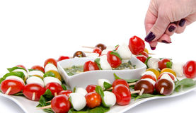 Hand dipping a skewer of cherry tomatoes and mozzarella in a vin Royalty Free Stock Image