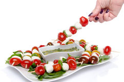 Hand dipping a skewer of cherry tomatoes and mozzarella in a vin Royalty Free Stock Photography