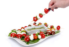 Hand dipping a skewer of cherry tomatoes and mozzarella in a vin Royalty Free Stock Photos