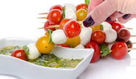 Hand dipping a skewer of cherry tomatoes and mozzarella in a vin Stock Photos