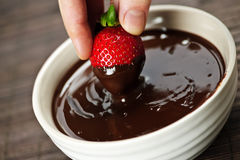 Hand dipping strawberry in chocolate Stock Photos