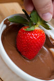 Hand dipping a strawberry in chocolate Royalty Free Stock Photos