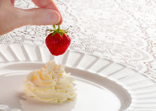 Hand Dipping Strawberry in  Whipped Cream Swirl Royalty Free Stock Image