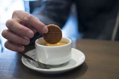Dipping a Dutch caramel waffle, called Stroopwafel, in coffee royalty free stock image