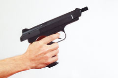 Hand with discharged pistol on white background Stock Photo