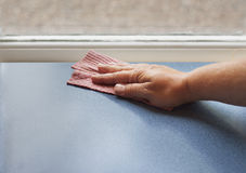 Hand with dish cloth cleaning surface. A hand holding a sponge wiping of a counter. Space for text stock photo