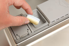 Hand with dishwasher tab Royalty Free Stock Images