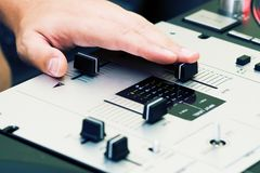 Hand of a dj adjusting the crossfader Royalty Free Stock Image