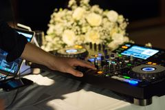 Hand DJ playing music at mixer closeup Stock Image