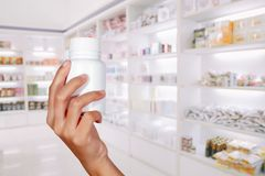 Hand of doctor holding medicine bottle on medicine cabinet and s. Tore medicine and pharmacy drugstore stock images