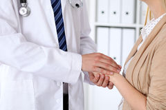 Hand of doctor  reassuring her female patient. Medical ethics and trust concept Stock Images