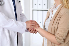 Hand of doctor  reassuring her female patient. Medical ethics and trust concept Stock Photos