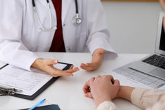 Hand of doctor reassuring her female patient. Medical ethics and trust concept Stock Photo