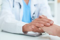 Hand of male doctor reassuring his female patient close-up. Medical ethics and trust concept. stock photography