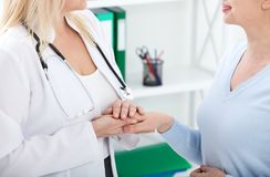 Hand of doctor reassuring her female patient. Medical ethics and trust concept. Handshake, hands closeup Stock Images