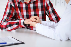 Hand of doctor  reassuring her male patient. Medical ethics and trust concept Royalty Free Stock Image
