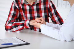 Hand of doctor  reassuring her male patient. Medical ethics and trust concept Royalty Free Stock Photo