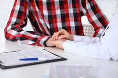 Hand of doctor  reassuring her male patient. Medical ethics and trust concept Stock Image
