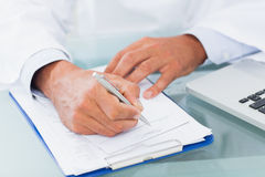Hand of a doctor writing on a prescription Royalty Free Stock Image