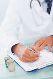 Hand of a doctor writing on a prescription pad Stock Photos