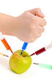 Hand does an injection in an apple Royalty Free Stock Photos