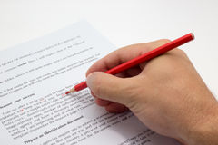 Hand doing proofreading on a faulty text with red pen Royalty Free Stock Photo