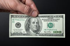 Hand and 100 dollar bill on a black background. Close-up.  royalty free stock images