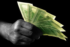 Hand with dollars. Businessman's hand with US dollar's on it over black stock photography