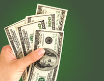 Hand with dollars. Isolated on green background Stock Photo