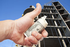 Hand with  dollars against the house under constru Royalty Free Stock Photo