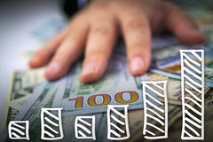 Hand on dollars with financial graph going up Stock Photo