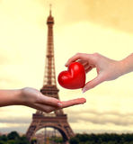 Hand donating heart. In the background Eiffel tower at sunset Royalty Free Stock Photography