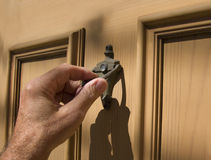 Hand on door knocker Stock Photography