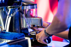Hand dosing fine ground coffee from the grinder stock images