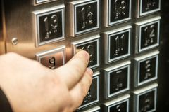 Hand drückt den Knopf des vorgewählten Bodens im Aufzug Stockfoto