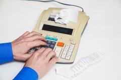 Hand drückt Tasten auf der schreibenden Rechenmaschine neben Lügenkontrollen Lizenzfreie Stockfotografie