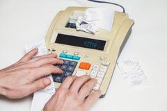 Hand drückt Tasten auf schreibender Rechenmaschine neben Lügenkontrollen Stockfotos