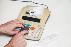 Hand drückt Tasten auf schreibender Rechenmaschine neben Lügenkontrollen Lizenzfreie Stockbilder