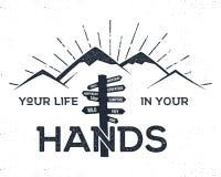 Hand dragen etikett med berg, vägvisaren och det inspirerande tecknet Arkivfoto